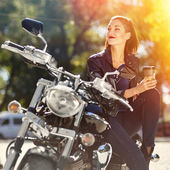 Biker girl in a leather jacket on a motorcycle drinking coffee — Stockfoto