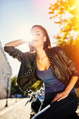 Biker girl in a leather jacket on a motorcycle — Stockfoto