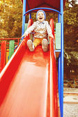 Little boy playing on children's slides — Stockfoto