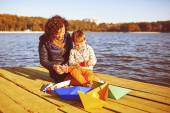 Mom and son playing with paper boats by the lake — Stock Photo