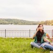 Two cheerful sisters sitting on the grass and blowing bubbles — Stock Photo #73347385