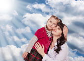 Young mother and her little daughter look up on a background clo — Stock Photo
