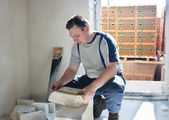 Man worker measures the ruler silicate brick — Stock Photo