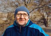 Ritratto di un uomo anziano sorridente che indossa occhiali, un cappello grigio un — Foto Stock