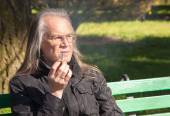 Elderly gray-haired man in glasses smoking a cigarette — Stock fotografie