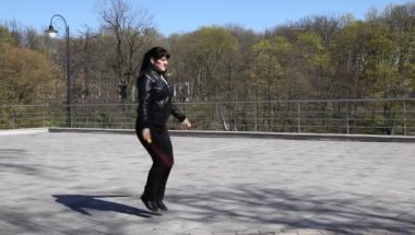 Young beautiful woman jumping rope in a city park — Stock Video