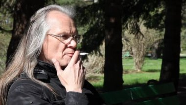 Elderly gray-haired man in glasses smoking a cigarette — Stock Video