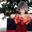 Young woman near new year tree with present — Stock Photo #56427301