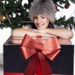 Young woman near new year tree with present — Stock Photo #56427323
