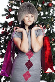 Young woman near new year tree makes shopping — Stock Photo