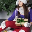 Young beautiful woman near new year tree with present — Stock Photo #58376647