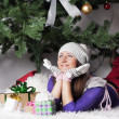 Young beautiful woman near new year tree with present — Stock Photo #58376683