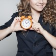 Businessoman holding clock in hands — Stock Photo #64700715