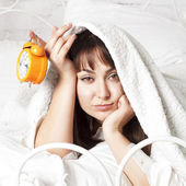 Young beautiful woman in bed with clock — Stock Photo