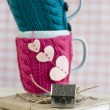 Two blue cups in blue and pink sweater with felt hearts — Stock Photo #52526843