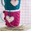 Two blue cups in blue and pink sweater with felt hearts — Stock Photo #52528231