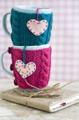 Two blue cups in blue and pink sweater with felt hearts — Stock Photo