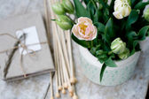 Bouquet of delicate pink tulips and needles for knitting on a wooden background — Stock fotografie