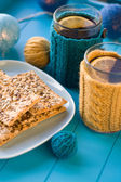 Two cups of delicious tea in knitted sweater yellow on blue background and cookies — Stock Photo