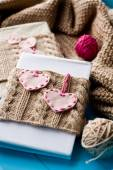 Two old pads in knitted cover with felt hearts lie next to the c — Stock Photo