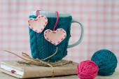 Blue cup in a blue sweater with felt hearts — Stock Photo