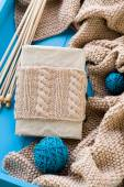 Old notebook with knitted wrap, beige knitted blanket and spokes — 图库照片