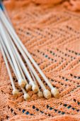 Many wooden spokes lie on an orange knitted plaid — Stock Photo