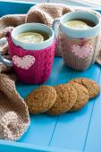Two blue cup of tea in knitted sweater with hearts felt standing — Стоковое фото