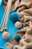 Wooden needles lie next to the bright tangle of threads and knit — Foto de Stock