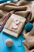 One old notebook in knitted cover with felt hearts lie next to t — Foto de Stock