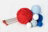 Colorful balls and needles for knitting lying on a white backgro — Stockfoto