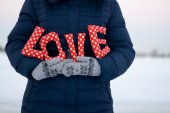"""Girl in blue down jacket and gloves holding a sign """"Love"""" — Stock fotografie"""