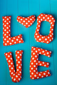 """The letters with red polka dot fabric """"LOVE"""" and heart on blue w — 图库照片"""