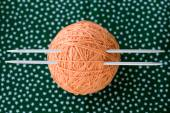 A bright orange ball of yarn and needles for knitting lying on a — Stock Photo