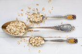 Three tablespoons of oatmeal lying on a white wooden background. — Stock Photo