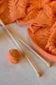 Jasny pomarańczowy plaid dzianiny, iglice i przędzy kulki na — Zdjęcie stockowe