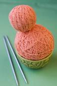 Two balls of pink yarn and knitting needles on a National Turkis — Foto de Stock