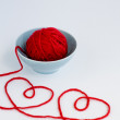 Two red hearts made from yarn, yarn ball of red and blue plate — Stock Photo #68486425