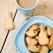 Sweet tasty cookies in the blue plate, a cup of coffee with milk — Stock Photo #72244605