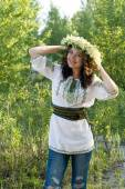 Portrait of a young beautiful in traditional Ukrainian embroidered shirt and a wreath of lilies of the valley on the head — Stock Photo