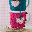 Two blue cups in blue and pink sweater with felt hearts — Stock Photo #77280556