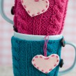 Two blue cups in blue and pink sweater with felt hearts — Stock Photo #77280516