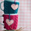 Two blue cups in blue and pink sweater with felt hearts — Stock Photo #77280550