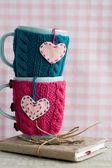 青とピンクのセーターを感じた心の 2 つの青いカップ — ストック写真