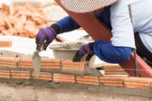 れんが造りの壁の建設現場で働く職人 — ストック写真