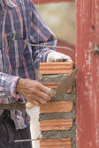 Bricklayer working in construction site of brick wall — Stock Photo