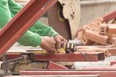 Worker cutting metal with grinder in construction site — Stock Photo