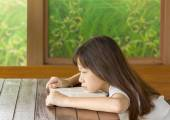 Asian gir tired on desk while learning — Stock Photo