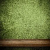 Wood table and green concrete wall — Stock Photo