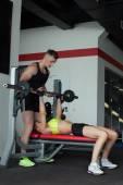 Yakışıklı adam kız halter egzersiz ile yardımcı olur — Stok fotoğraf